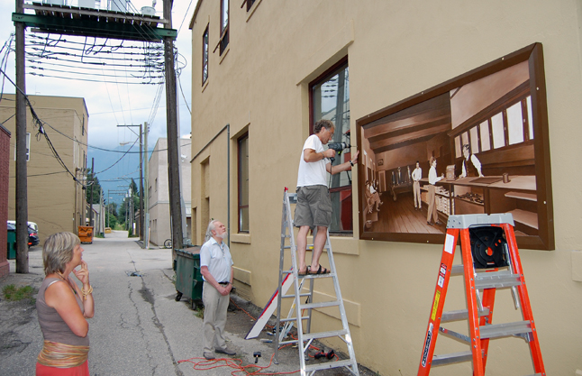 Ken attaches the first mural to the wall under the watchful eyes of painter Tina Lindegaard and David Evans. David F. Rooney photo
