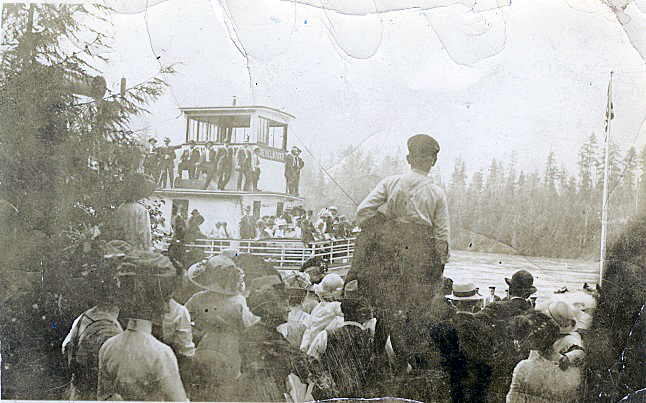 A stroll along the streets of downtown Revelstoke offers glimpses into the city's past as museum-style photographs and interpretive panels hang in empty storefront windows, providing an historical walking tour for history lovers. In this photo the SS Revelstoke Steamboat landing at Columbia Park Fairground attracts a crowd. Photo 167 courtesy of the Revelstoke Museum and Archives