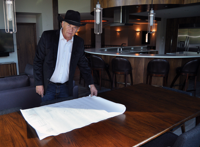 Peter shows the floor plans for the 1,000 square-foot addition to his home. The dining room is, of course, part and parcel of the open plan living and dining area. David F. Rooney photo