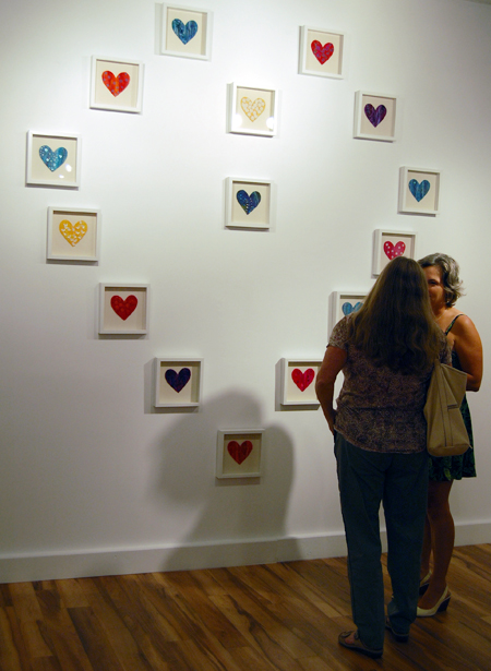 Carol Palladino and Carmen Segger chat in front of Jackie Penergast's work, Love, Love Changes Everything. David F. Rooney photo