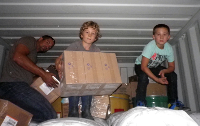 Landon, Gabe, and Liam play shift around smaller boxes to maximize the available space within the container. Sue Leach photo