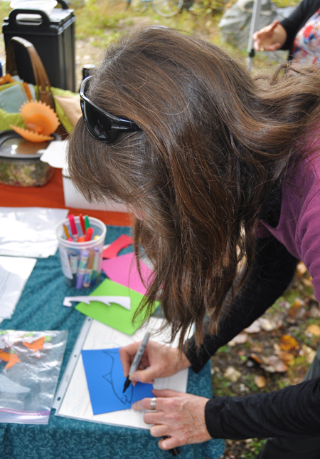 Biologist Karen Bray draws a Kok,anee-shaped name badge at the Kokanee Fish Festival at Bridge Creek on Friday, September 26. Karen was one of several people who volunteered their time to help child enjoy the natural wonder and beauty of spawning Kokanee. David F. Rooney photo