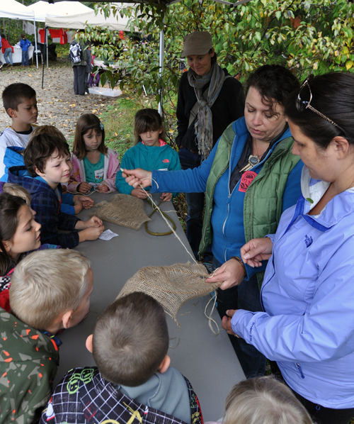 Elementary Aboriginal Student Assistant Lisa Moore (right, in blue) shows students how the native people who lived here before European settlement in the 19th century created fishing nets. David F. Rooney photo