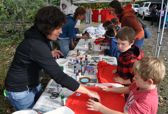 Simone Palmer helps a couple of youngsters decorate their T-shirts with salmon-shaped stamps at the Kokanee Fish Festival's art station. David F. Rooney photo