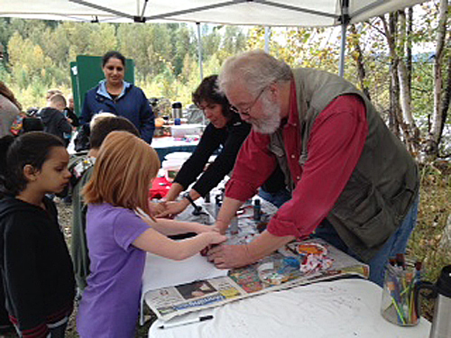 David Rooney helps a young girl stamp her T-shirt during the fish festival. Tammy Voykin photo