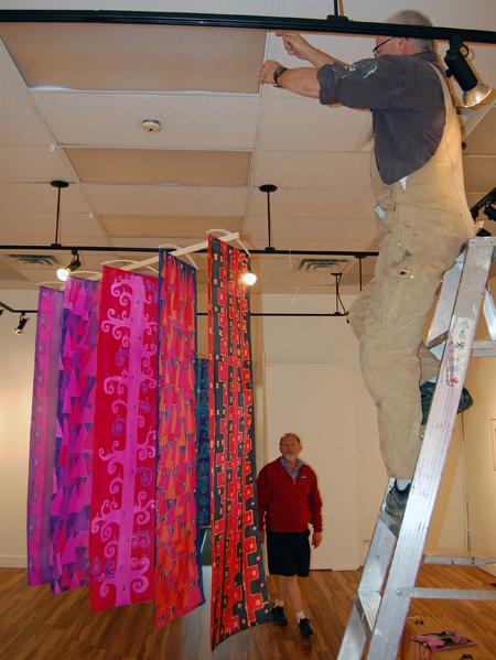 Kan Talbot hangs some of Jackie's beautiful scarves. David F. Rooney photo