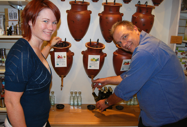 Crescendo's Daniel Weber draws some specialty vinegar from a an amphora for Big Mountain Kitchen and Linen proprietor Nicole Cherlet on Friday during the opening of a major display of Cresendo's product line at Nicole's progressive and well-appointed shop on Mackenzie Avenue. Crescendo did have its own store on First Street West but Daniel and his partner, Elvira Bruner, have since moved to Kelowna where they cater to a larger market. Still, it's nice to see that their very high quality oils, vinegars and salts are still available in Revelstoke. David F. Rooney photo
