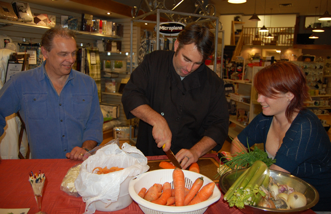 Look, Ma! No blood! Crescendo's Daniel Weber (left) and Big Mountain Kitchen and Linen proprietor Nicole Cherlet watch as Nicole's husband Glenn carefully — But oh so swiftly! — chops carrots for a cooking demonstration at Big Mountain on Friday, October 17. Glenn was so fast with the knife that you had to wonder if he wasn't worried about slicing off a finger. Well, that's actually happened to him. Fortunately, he has had a lot of practice since that long-ago mishap.  David F. Rooney photo