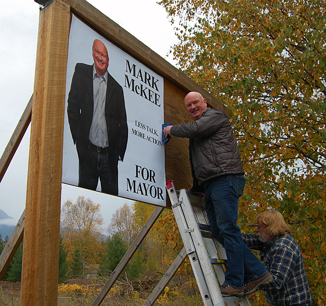 Garry Gregg secures the ladder as Mayoral candidate Mark McKee puts up one of his new election signs. This one is at the intersection of Airport Way and Nichol Road. Other large signs will be going up at strategic intersections around town. David F. Rooney photo