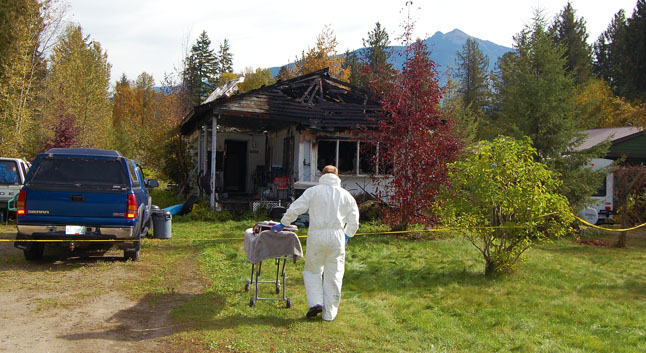 A local man died in an early-morning fire at 1095 Lundell Road in the Big Eddy on Thursday, October 9. Here Gary Sulz enters prepares to enter the house. David F. Rooney photo