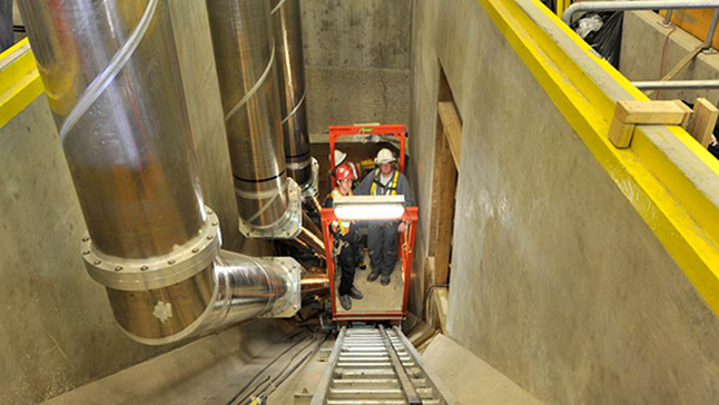 One challenge was to install conductors in three narrow 183-to-305-meter long tunnels from the underground generating units to the above-ground switchgear building. A small cart on rails was used to transport workers up and down each tunnel. Dusty Veideman/BC Hydro photo