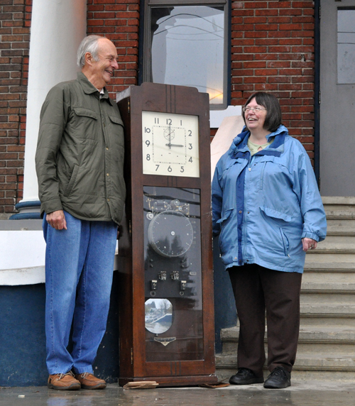 School Board Trustee Jeff Nicholson got Museum Curator Cathy English to dash through the rain to meet him on the steps of historic Mountain View School on Friday, October 31, by offering her something she could not resist: a large clock that used to keep time in MVE's staff room. The time piece was manufactured by IBM back in the 1950s. Hundreds of items large and small are on offer during an all-day Saturday, November 1, monster garage sale in MVEs gymnasium on Second Street West.  David F. Rooney photo