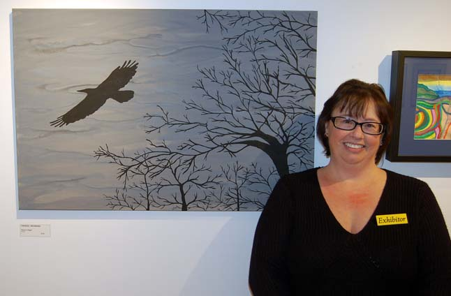 Theresa Browning poses with her painting, Raven's Flight. Only Natural is this RSS art teacher's first-ever exhibition. Among the many works she is showing at the gallery are two large floral pieces that are particularly good. David F. Rooney photo