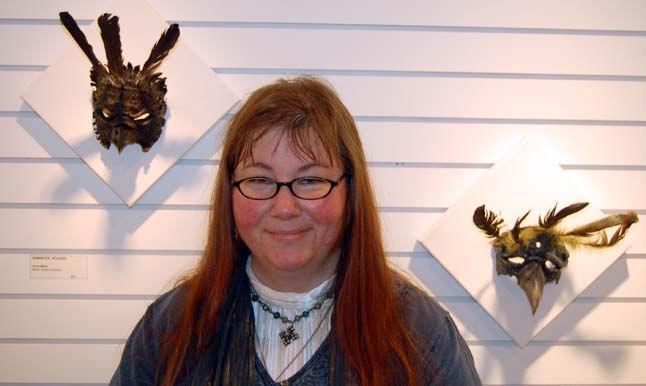 Jennefer Rogers poses with her Crow (left) and Raven masks. Much of her work is based on mythology and fantasy and often has an intriguingly dark tint to it. David F. Rooney photo