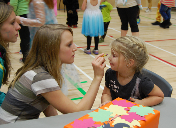 Halle Wolgram decorates young Cadence McAstocker's face at the face-painting table.  David F. Rooney photo
