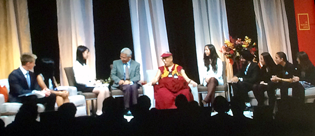 """MacKenzie (far left) on stage with the Dalai Lama and other guests at the Heart-Mind Summit, which was held at John Oliver Secondary School. The event sought to teach students and adults that """"the qualities that make up Heart-Mind well-being can be deliberately fostered in families, in schools and in communities."""" School District 19 Superintendent Mike Hooker was so impressed with MacKenzie's performance that the Board of Trustees is send him a letter of commendation for it. Photo courtesy of Mike Hooker."""