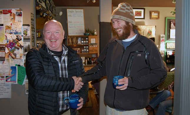 Mayor-elect Mark McKee (left) and electoral opponent Michael Brooks-Hill share a laugh and a post-election shake at Sangha Bean Cafe on Monday morning. Michael congratulated Mark on his victory and was, in turn, encouraged to get directly involved in promoting civic progress by getting involved in one or more City committees. The two men may embody different personal styles and political demographics but they share a love for Revelstoke and a desire to see it succeed. David F. Rooney photo
