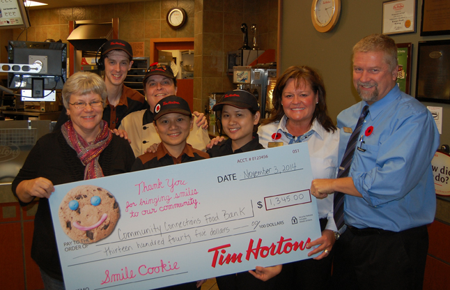 Patti Larson (left), manager of the Community Connections Food Bank was all smiles as she posed with this $1,345 cheque from Tim Hortons, represented here by franchise owners Brian and Donna Lecomte (right) and employees Byron Tallis, Katrina Nelson, Laarni Iaccino and Shella Cabugos. The money was raised through Timmy's annual Smile Cookie campaign. David F. Rooney photo