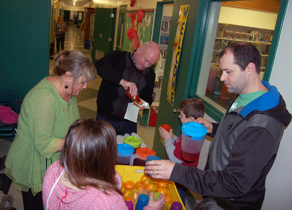 Easy on the ketchup? Mayor Mark (center) adds condiments to a student's hot dog at Columbia Park Elementary School on Thursday morning. His Worship talked to students about the municipal election and the role of local government before joining parents Tracey Thibeault (left) and Seanan Sharp to serve up the dogs to the hungry youngsters. David F. Rooney photo