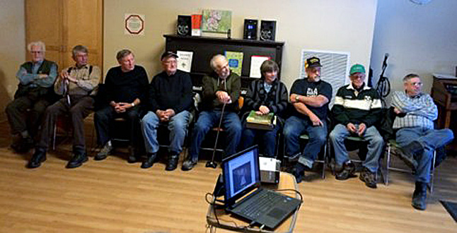 Members of the Retired Railroaders Coffee Club are telling tales far and wide in Revelstoke this winter. Here, members (left to right) Les Handley, Ed Jaatteenmaki, Louis Deschamps, Tom McMahon, Ernie Ottewell, Shelley Koski, Ed Koski, Jack Carten, and James Walford talk about the past during a visit to Mount Cartier Court.  George Hopkins photo