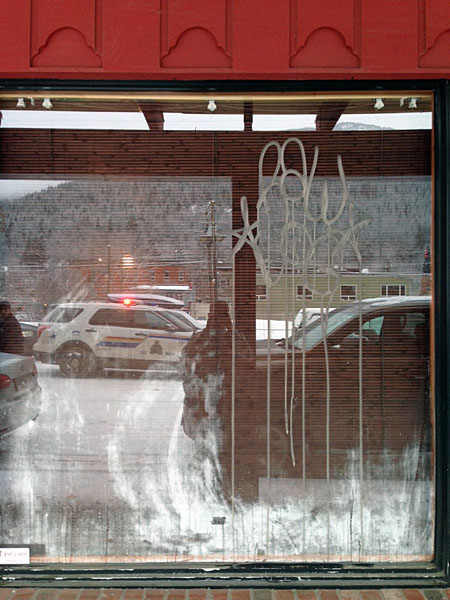 Three local businesses were struck with graffiti early Friday morning. According to local RCMP Staff Sgt.. Kurt Grabinsky all three businesses are located in the 100 block of Second Avenue, East and West. All three had extensive paint, pen or glass etching damage on the glass windows. The material used is acidic, resulting in the need to replace the glass at each location in order to remove the writing. Photo courtesy of the Revelstoke RCMP