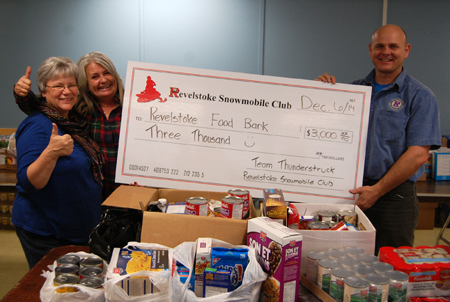 An enthusiastic Cathy Burke and Daniel Kellie of the Revelstoke Snowmobile Club surprised Patti with a generous $3,000 cash donation plus boxes of groceries for the Food Bank's Christmas Hamper program on Friday, December 5. David F. Rooney photo