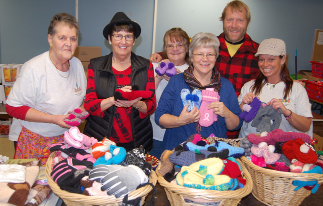 Christmas Hamper Depot volunteers Gladys Dyer (left), Joan Thatcher, Ben Blair and Lisa Donovan (righgt) pose with Patti Larson and Carol Sakamoto on Friday when Carol brought in naskets containing 150 mittens, scarves, slippers and hats knitted by local volunteers with Carol's annual home-grown Mittens for Kids campaign. This is a tremendous example of the efforts made by local people to support their less fortunate friends and neighbours. David F. Rooney photo