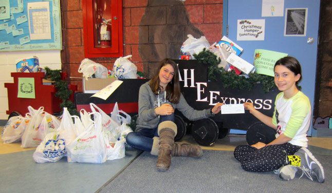 Student Council co-Prime Ministers Hannah Vickers and Catherine Gingras of Arrow Heights Elementary School sit in front of the AHE Express food train. They joined Principal Todd Hicks in saying thank you to AHE community families who donated food and cash for the Community Connections Food Bank.  Over $295 in cash was donated as well as a trainload of food. Photo courtesy of Todd Hicks
