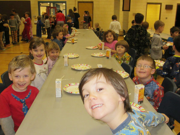 Mariah Skelton, Anya Wolfe-Patrick, Ivo Keerak, Levi Maloney, Corbin Kernaghan, Spencer Grimsdell, and Bella Stevenson are eating their delicious pancakes at Arrow Heights Elementary School's pancake breakfast in the gym on February 10th, 2015. Photo By Emily MacLeod and Amelie Delesalle