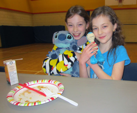 Megan Hoshizaki and Ava Keerak show off their stuffies in the gym at Arrow Heights Elementary School's pancake breakfast. Photo By Emily MacLeod and Amelie Delesalle