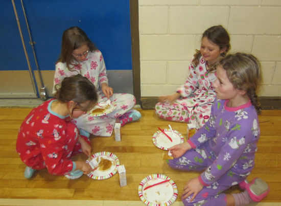 Rachel Grabinsky, Rebecca Grabinsky, Alexandra Luxmore and Ruby Seccoya having a breakfast picnic in the gym at the Arrow Heights pancake breakfast to kick-off Spirit Week. Photo By Emily MacLeod and Amelie Delesalle