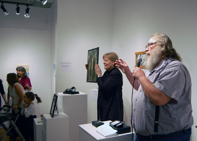 Rob Lamont did an excellent — and very entertaining — job as a live auctioneer, That's Visual Arts Centre Executive Director Jackie Pendergast displaying one of the works up fr grabs. David F. Rooney photo