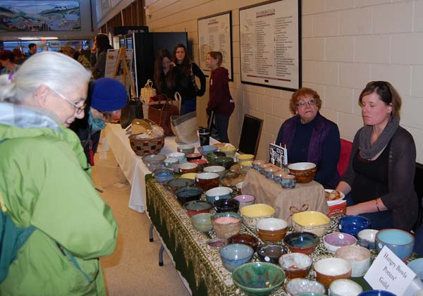 Sandra Flood (left) considers some of the pottery for sale by members of the Pottery Guild. Sandra is a potter, too, and had some interesting pieces in the sale, as did Tanis Rebetoy and Melissa Klages (right). David F. Rooney photo