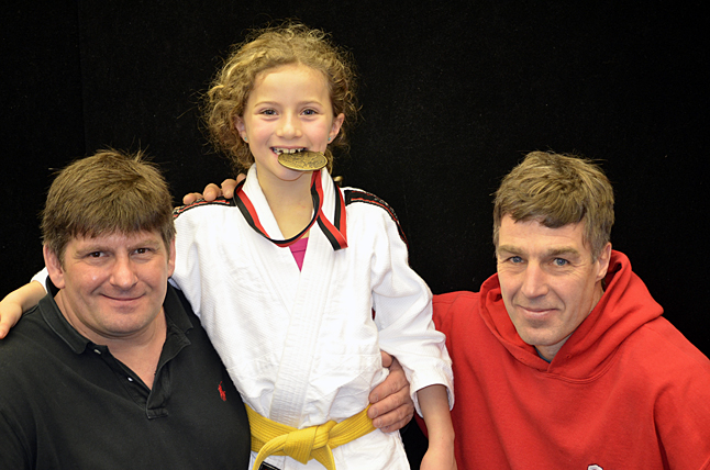 Ruby Serrouya enjoying her snack, flanked by coaches Ted Allain (left) and Cornelius Suchy. Photo courtesy of the Revelstoke Judo Club