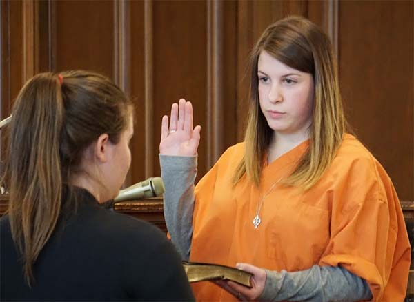 Casey Hunt in the orange is sworn in by Court Reporter Hanah Renaud as a witness for the prosecution. Jeff Colvin photo