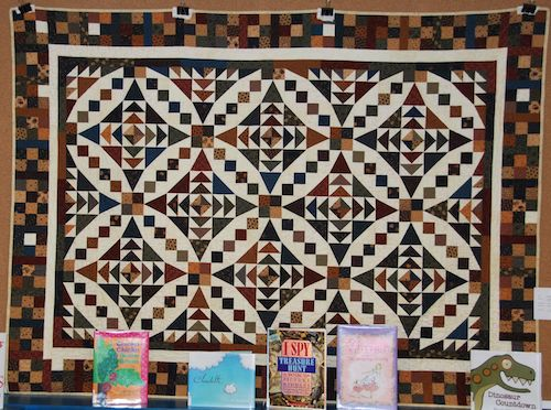 Fall Splendour by Darlene Dabell. Machine quilted by Connie Baker. (Sorry about the books--it is a library display.)