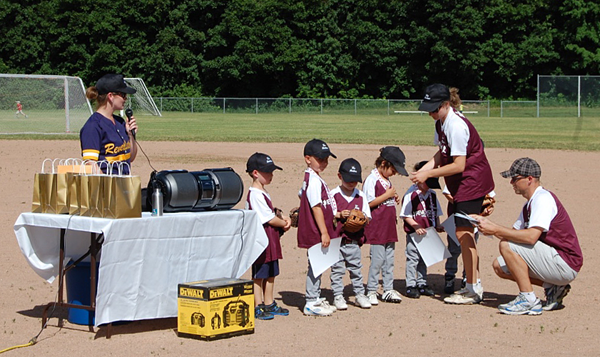 Coaches Diana Bostock and Clark Travers present the kids of Beginner Burgundy with their swag at the windup as Minor Ball President Mandy McQuarrie praises their efforts. David F. Rooney photo