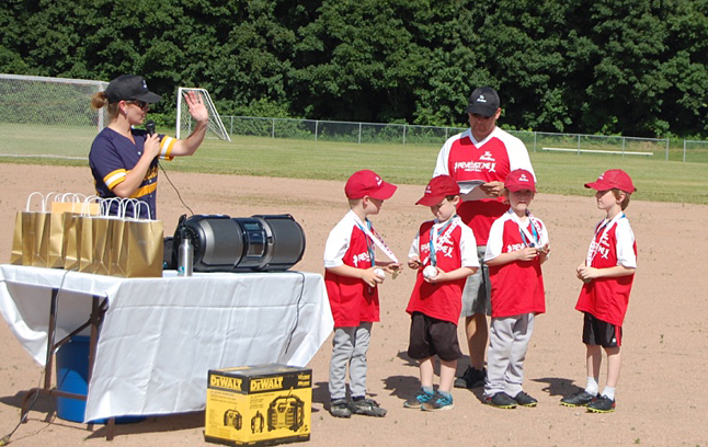 The kids of the Rally Cap Red Team compare medals. Jamie Adam and Greg Kenyon were their coaches this year. David F. Rooney photo