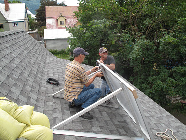 Friends Sonny Pedersen and John Bafaro set up the panel on the roof. Because it's a temporary project, the structure will be weighed down with sand bags. Laura Stovel photo