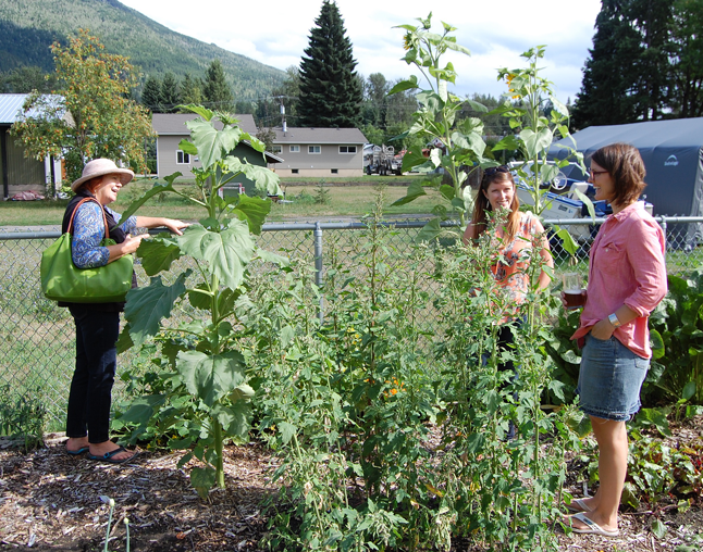 Karilyn (right) talks with friends beside one of her unusual cops — quinoa. Those are the tall plants in the foreground that look rather like pigweed. David F. Rooney photo