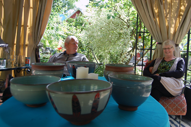 Jim Cook and Sharon Kelley relax in the pavilion and admire the ceramics on display by Kaitlin Murphy of Jumping Creek Pottery in their garden on Second Street West. David F. Rooney photo