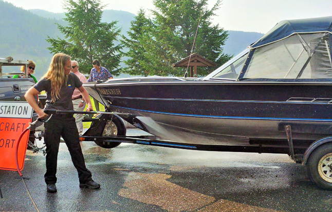 Ember Heidt, Compliance and Enforcement Officer with the Conservation Officer Service demonstrates how to decontaminate a boat with suspected invasive mussels. Photo courtesy of the Columbia Basin Trust