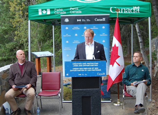 MP David Wilks (left) and Nick Irving (right), superintendent of Mount Revelstoke and Glacier National Parks, listen as Colin Carrie, parliamentary secretary to Environment Minister Leona Aglukkaq, speaks during the announcement of a major spending package for the two parks. David F. Rooney photo