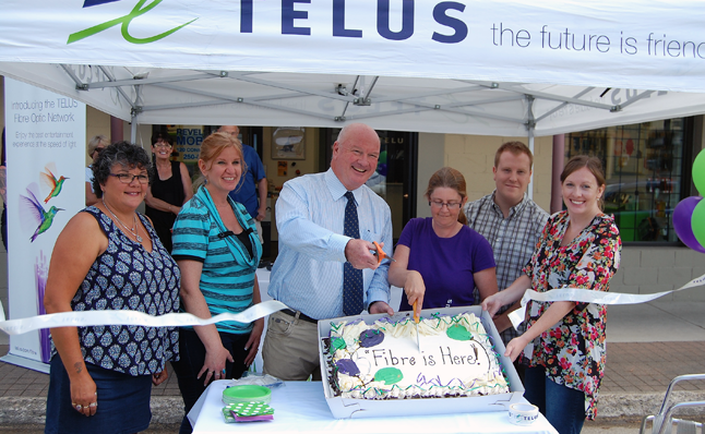With a snip of his scissors Mayor Mark McKee officially marks the moment on Tuesday, July 14, that Telus's new high-speed Internet service begins working in Revelstoke while Telus Regional Marketing Manager Clare Adams starts cutting the celebratory cake. The brief ceremony took place at Shannon Van Goor's (that's Shannon on the right holding the cake) Telus Mobility store on Connaught. The first service area in the city includes the downtown core west of Connaught Avenue to Pearson Street  from Victoria Road. Other service areas will become active in the days to come. David F. Rooney photo
