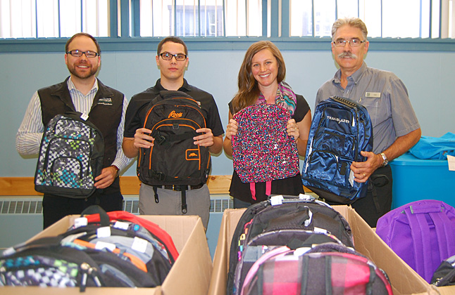 """Staff at the Revelstoke Credit Union are great supporters of all kinds of community efforts, especially those involving kids. This Friday, August 21, Julia Marshall, Frank, Tyler Maki and Colby Morin brought 46 backpacks to the Food Bank for distribution to children from low-income families. Backpacks for kids at Columbia Park and Begbie View elementary schools contained vouchers for school sullies from those schools. Kids at Arrow Heights Elementary and Revelstoke Secondary received supplies directly. Either way it helps all kids enjoy a fresh start to the school year. Moms who dropped by to pick up their children's backpacks were deeply touched by the effort put on by the Credit Union's staff.  """"This means a lot to me,"""" one mom said. """"It really does."""" David F. Rooney photo"""