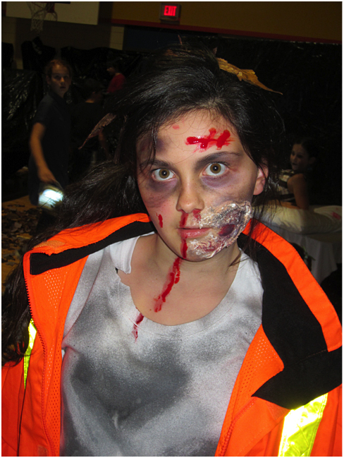 Cassidy Legebokow- zombie construction worker, frightens the community with outstanding makeup and costume. Photo and caption by Emily MacLeod and Amelie Delesalle AHE student reporter-photographers