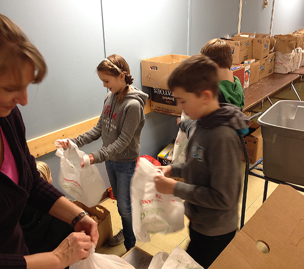 Cassie Wolgram, Sam Folden and Cole Bibby help assemble food hampers at the Community Connections Food Bank. Eleanor Wilson photo
