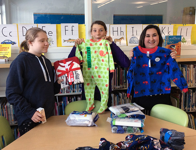 Morgan Hamilton, Jaclyn Elliott and Emjai Deschamps help sort through donations of new pyjamas socks and underwear. Eleanor Wilson photo