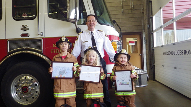 Emma Hein of Begbie View Elementary, Jalen Pehowich of Arrow Heights Elementary and Poppy Eadie of Columbia Park Elementary were this year's Fire Chief for a Day.  The kids, shown here posing with Chief Rob Girard, won after their posters about the importance of having a fire alarm were chosen as the best from a field of 96 submissions.  Emma, Jalen, and Poppy were picked up at school on Thursday, November 5,  in Ladder Truck No. 6 and spent the afternoon as the City's Fire Chiefs. The young chiefs received a tour of the fire hall, prize packages and participated in fire department activities. The three chiefs were then treated to a pizza lunch with Fire Chief Girard and Revelstoke's career firefighters. Photo courtesy of the Revelstoke Fire Rescue Service