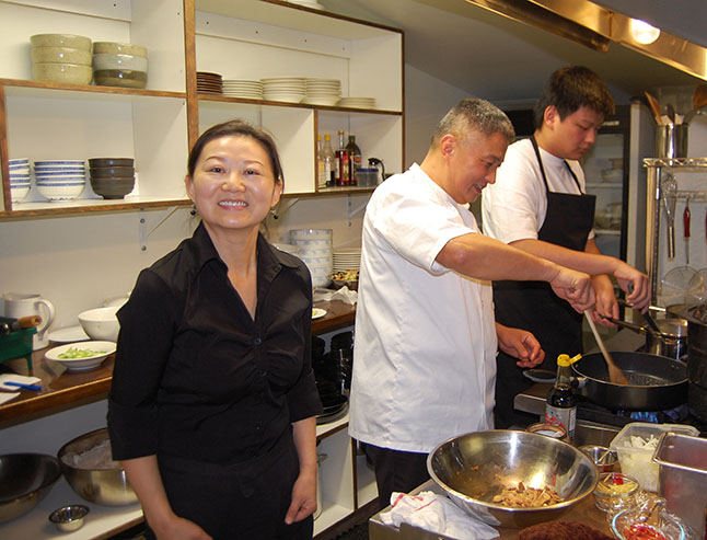 Lu Si beams as her husband, Kevin, and their son whip up some culinary delights for the lunch-hour-crowd at their new restaurant, Kevin's Kitchen. David F. Rooney photo